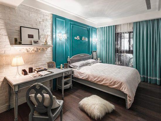 青色系的窗帘与背景自然而然地勾勒出睡眠区与工作区,壁灯与台灯的