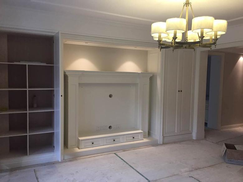 客厅电视机背景油漆阶段,旁边是两个现场木工打的储物柜,中间做了壁炉
