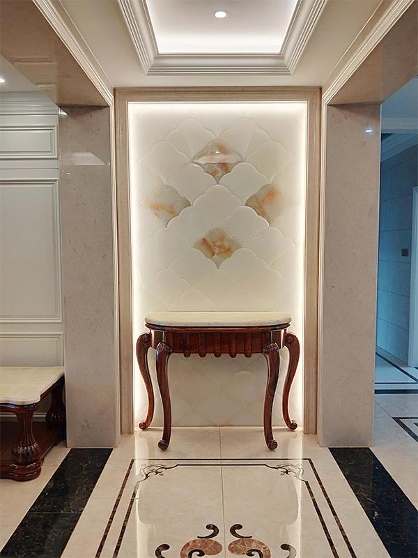 进门后的玄关处背景采用的玉石材质,家中的墙面也是一律的瓷砖,暖光
